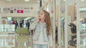 Leuke meisje dragende het winkelen zak, die bij de wandelgalerij lopen stock videobeelden
