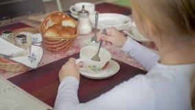 Leuke meisje het drinken thee in koffie licht ontbijt Weinig Kaukasisch meisje die een slokje van thee nemen bij de koffie stock videobeelden