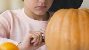 Leuke meisje het schilderen hefboompompoen, voorbereiding voor Halloween-vooravondpartij, geheimzinnigheid stock videobeelden