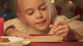 Leuke meisje het schrijven brief aan Santa Claus of prentbriefkaar aan wens vrolijke Kerstmis stock footage