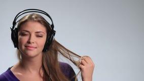 Leuke meisje ontspannende het luisteren muziek met hoofdtelefoons stock video