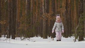 Leuke meisjedalingen neer op de sneeuw in de winterbos stock video