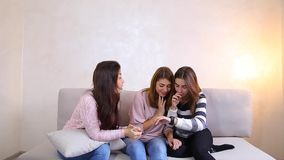 Leuke meisjes die bekijken en modieus slim horloge bestuderen, die op laag in heldere slaapkamer zitten stock video