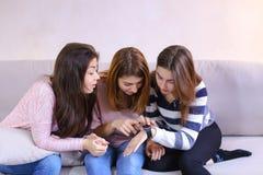 Leuke meisjes die bekijken en modieuze iWatch bestuderen, die op mede zitten Royalty-vrije Stock Fotografie