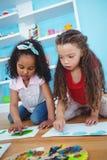 Leuke meisjes die met hun vingers schilderen Stock Afbeeldingen