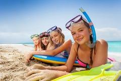 Leuke meisjes die met lichaamsraad leggen op zandig strand Stock Foto