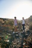 Leuke meisjes die onderaan rotsachtige weg lopen Stock Afbeelding