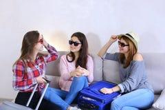 Leuke meisjes die op reis gaan en koffers op laag binnen achterin voorbereiden Stock Afbeeldingen