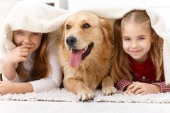 Leuke meisjes die pret met hond het glimlachen hebben Stock Afbeeldingen