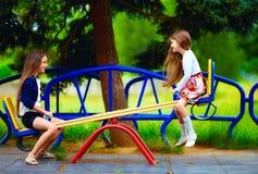 Leuke meisjes die pret op geschommel hebben bij speelplaats Stock Foto