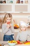 Leuke meisjes die salade proberen te koken en te helpen baren Royalty-vrije Stock Foto's