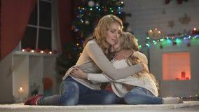 Leuke meisjes ontbrekende vader en het koesteren van mamma, die dichtbij mooie Kerstmisboom zitten stock video