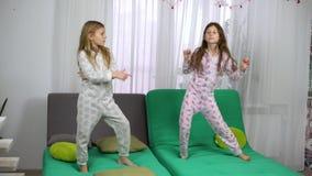 Leuke meisjes in pyjama's die op bank dansen stock video