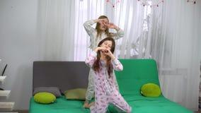 Leuke meisjes in pyjama's die op bank dansen stock footage