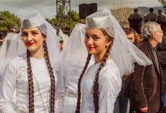 Leuke meisjes in traditionele witte Georgische kostuums klaar voor het dansen prestaties in Georgië Stock Foto