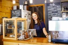 Leuke meisjesbarista die de rekening in het koffiehuis tellen op de tablet royalty-vrije stock afbeeldingen