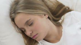 Leuke meisjesslaap comfortabel op zacht bed linens, kalme en stille droom hoogste mening stock videobeelden