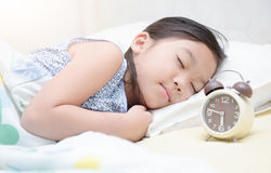 Leuke meisjesslaap op bed met wekker Stock Foto's