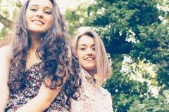 Leuke meisjesvrienden die op een boomstam zitten Stock Fotografie