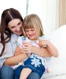 Leuke meisjeszitting op de overlapping van haar moeder stock fotografie