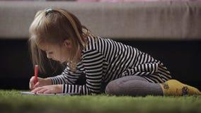 Leuke meisjetekening met potlood in kinderdagverblijf De kleine prinses speelt door het patroon met rode pen te schilderen Blonde stock footage