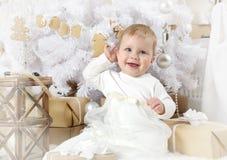 Leuke meisjezitting onder een Kerstboom stock afbeeldingen