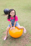 Leuke meisjezitting op een grote gele bal Stock Fotografie