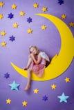 Leuke meisjezitting op een grote maan stock afbeeldingen