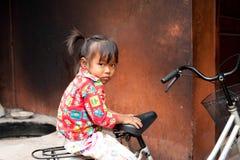Leuke meisjezitting op fiets bij straat De stad in van Siem oogst, Kambodja Stock Afbeeldingen