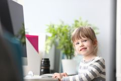 Leuke meisjezitting thuis bij het worktable kijken in camera royalty-vrije stock afbeelding
