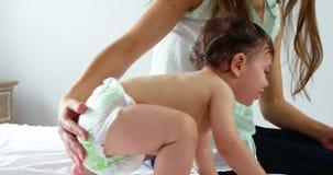 Leuke moeder die dicht toezicht op haar baby houdt die op een bed speelt stock footage