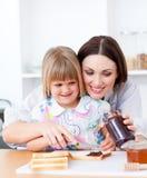 Leuke moeder die haar dochter in de keuken helpt Stock Fotografie
