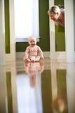 Leuke mollige baby die op vloer bij mamma lacht royalty-vrije stock afbeeldingen