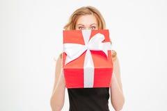 Leuke mooie jonge vrouw die haar gezicht verbergen die huidige doos behing Royalty-vrije Stock Foto's