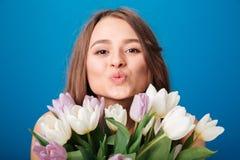 Leuke mooie jonge vrouw met boeket van tulpen die kus verzenden Royalty-vrije Stock Afbeelding