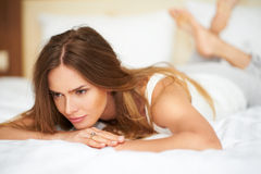 Leuke mooie vrouw die op bed in slaapkamer liggen Royalty-vrije Stock Foto