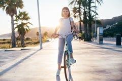 Leuke mooie vrouw op fiets op zonsondergang stock afbeeldingen
