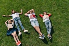 Leuke multi-etnische jonge geitjes die boeken op groen gras in park lezen stock fotografie