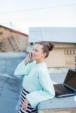 Leuke onderneemster die op de telefoon spreken die zich op het dak van het huis in de oude stad bevinden Naast het zijn laptop, s stock fotografie