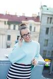 Leuke onderneemster in oogglazen die op de telefoon spreken die zich op het dak van het huis in de oude stad bevinden Naast het z stock foto