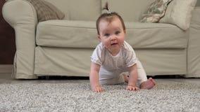 Leuke onhandige baby die en camera op vloer glimlachen bekijken stock video