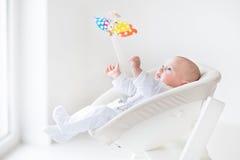 Leuke pasgeboren babyjongen die op kleurrijk mobiel stuk speelgoed letten stock afbeeldingen