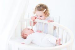 Leuke pasgeboren babyjongen die op zijn peuterzuster letten bevindend bij hallo royalty-vrije stock foto's