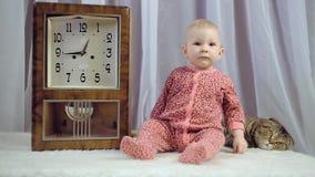 Leuke pasgeboren babymeisje en klok stock footage