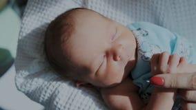 Leuke pasgeboren babyslaap vreedzaam op de moedershanden Sluit omhoog stock footage