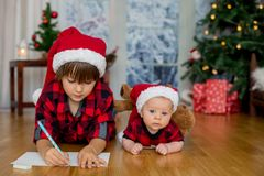 Leuke pasgeboren en zijn oudere broer, het schrijven brief aan Santa Clau royalty-vrije stock foto