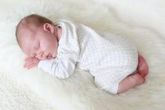 Leuke pasgeboren meisjesslaap op bontplaid Stock Afbeeldingen