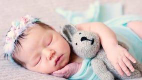 Leuke pasgeboren weinig baby ligt op bed met favoriet pluchestuk speelgoed stock video