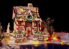 Leuke peperkoekfamilie dichtbij groot snow-covered peperkoekhuis stock foto's