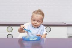 Leuke peuter in een blauwe slab die banaan in de moderne keuken eten stock foto
